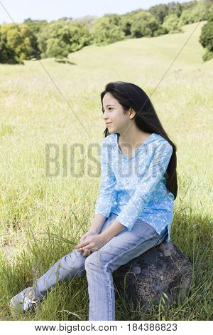 Hispanic girl sitting on rock in field