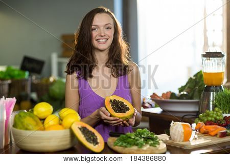 Smiling shop assistant holding half papaya at the counter in health grocery shop