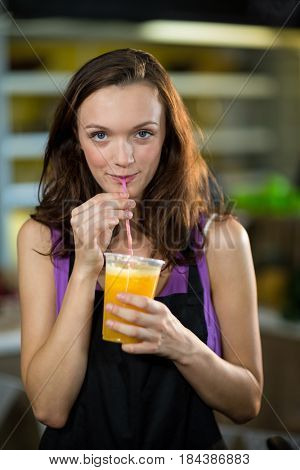 Shop assistant having fresh fruit juice at health grocery shop