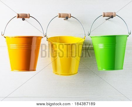 Bucket list concept. Three colorful buckets hanging on white wooden wall