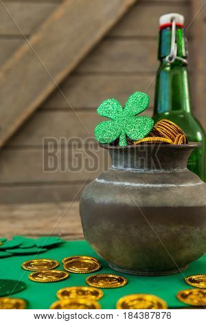 St. Patricks Day shamrock, beer bottle and pot filled with chocolate gold coins on wooden table