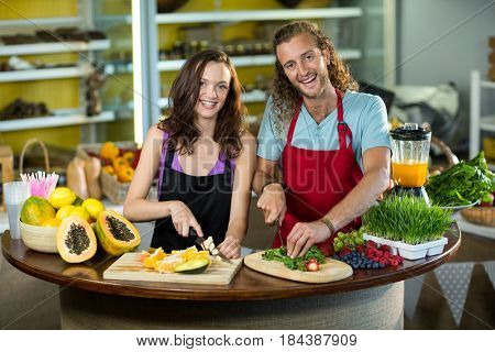 Two shop assistant chopping vegetables and fruits at counter in health grocery shop
