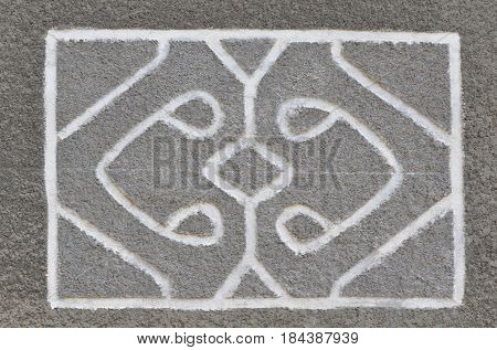 An abstract relief pattern is depicted on a cement wall coat.
