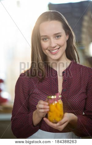 Portrait of a shop assistant holding a jar of pickle in grocery shop