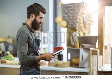 Salesman using digital tablet at counter in grocery shop