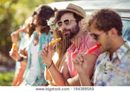 Group of friends eating ice lolly in park