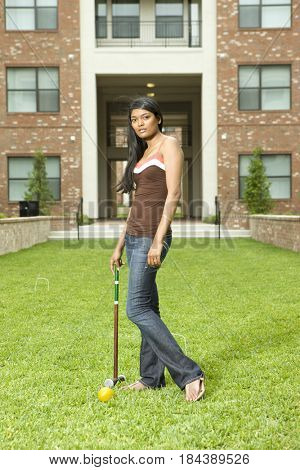 Mixed race woman standing on lawn with croquet mallet