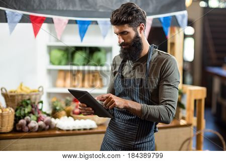 Vendor using digital tablet at the counter at grocery store
