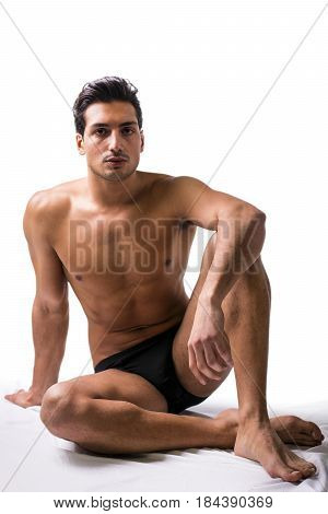A handsome latin young man sitting naked on floor, wearing only underwear. Muscular build
