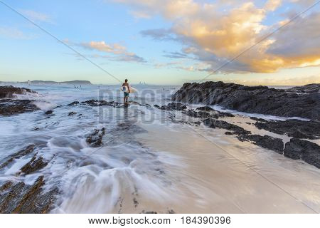 Surfer standing at the end of Currumbin Rock Gold Coast, checking out the surf at high tide.