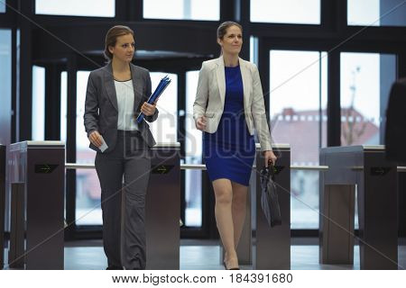 Business executives passing through turnstile gate at office