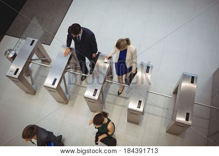 Top view of business executives passing through turnstile gate