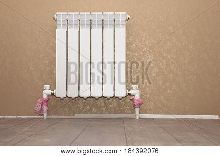 Heating radiator in a room with laminated wooden floor in a new apartment or house