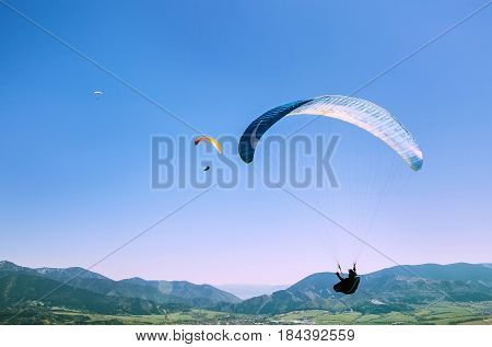 Flying paragliders in the blue sky .