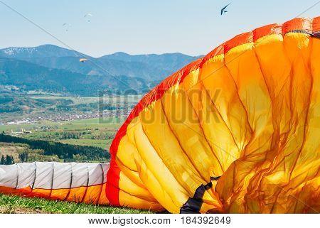 Orange parachute on the mountain hill .