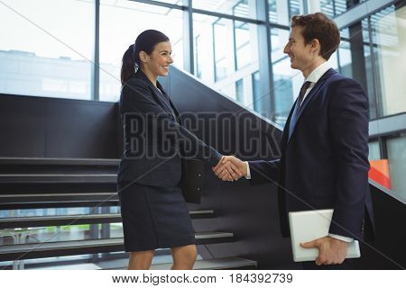 Business executives shaking hands on stairs at office