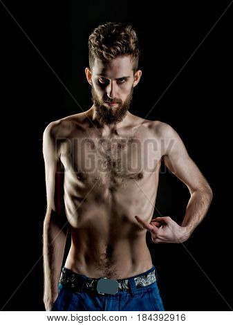 handsome bearded man or hipster guy dieting with serious face and bare slim or thin body chest and torso with anorexia isolated on black background