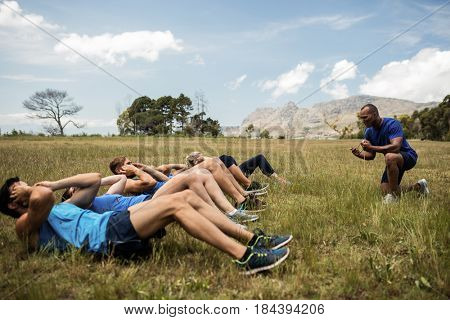 Fit people performing crunches exercise in bootcamp
