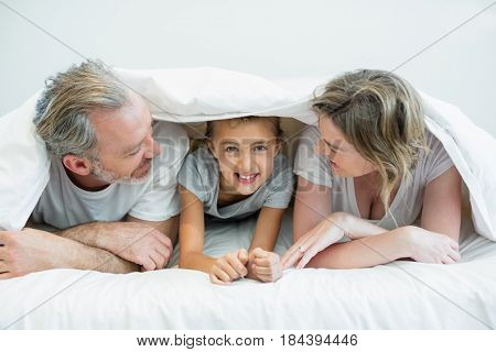 Portrait of happy family lying under blanket on bed in bedroom at home