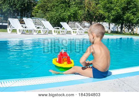 Little Boy Is Playing Next To A Pool