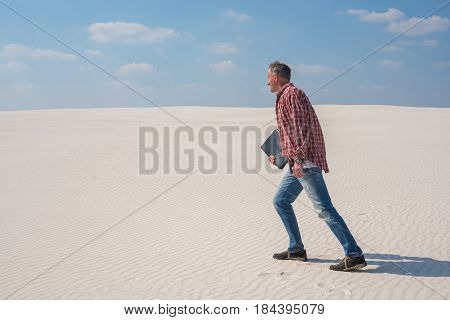 Joyful Energetic Man Is Walking Through The Desert With A Laptop