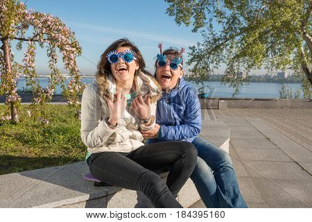 Sporty Mother And Adult Daughter In A Funny Sunglasses Are Expressively Laughing