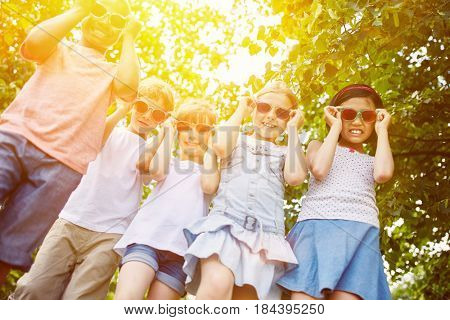 Cool group of kids as interracial friends with sunglasses in summer