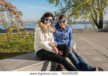 Portrait Of Happy Mother And Adult Daughter In A Funny Sunglasses