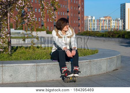 Happy Young Woman Rests After Roller Skating