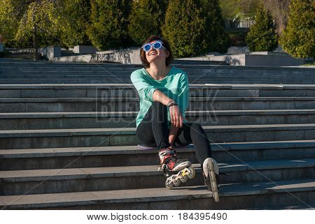 Joyful Girl In A Funny Sunglasses Expressively Laughs After Rollerblading