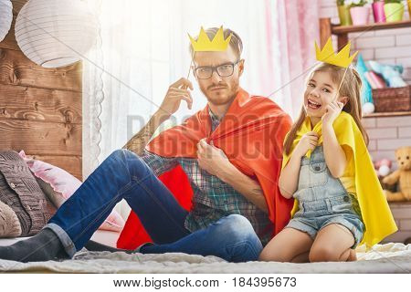 Funny time! Father and his child are playing at home. Cute girl holding paper crown on stick and pretend of princess. Family holiday and togetherness.
