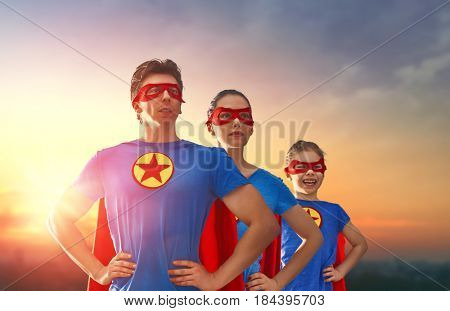 Mother, father and their daughter are playing outdoors. Mommy, daddy and child girl in an Superhero's costumes. Concept of super family.