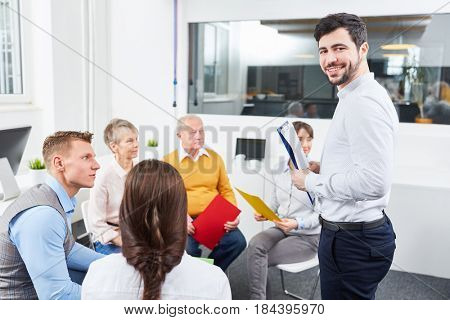 Man as coach in team building workshop with team in office