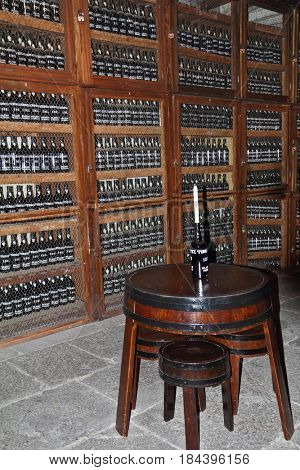 MADEIRA  ISLAND, PORTUGAL - OCTOBER 8, 2011: Wooden shelves with bottles of wine. Storage space for an expensive aged wines - Madeira. Round table with a bottle, which is inserted the candle