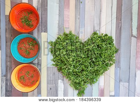 Tomato Gazpacho Soup In Colored Bowls On A Wooden Table