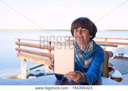 Woman Is Sitting On The Veranda On The Sea Shore, Using A Tablet