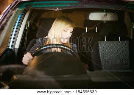 Portrait Blonde Woman Sitting Behind Wheel In Driver's Seat Of Blue Car. Hands On Handlebars, Drivin