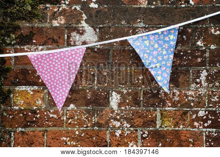 Festive floral printed bunting hanging against old brick wall