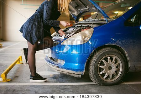 Woman Near Car's Hood. Young Blonde In Covered Parking Of Shopping Center, Stands Near Car With Engi