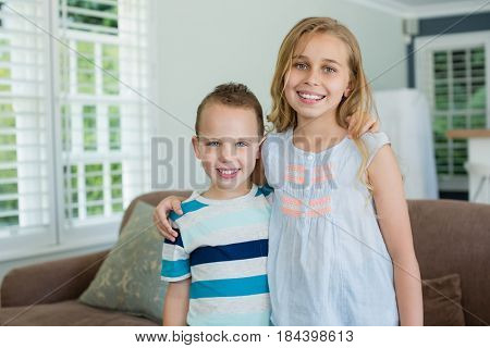 Portrait of smiling sister and brother standing with arms around in living room at home
