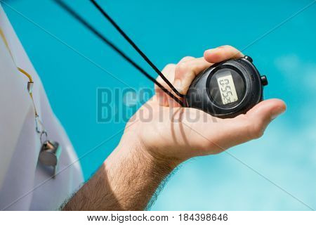 Mid section of swim coach holding stopwatch near poolside on a sunny day