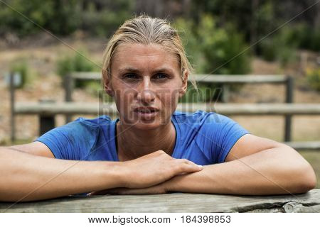 Portrait of woman leaning on a hurdle during obstacle course