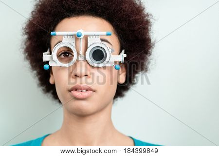 Woman having eyesight test with phoropter for new glasses at optician or eye doctor specialist