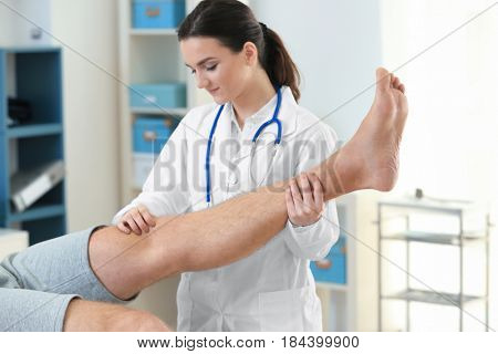 Orthopedist examining patient in clinic