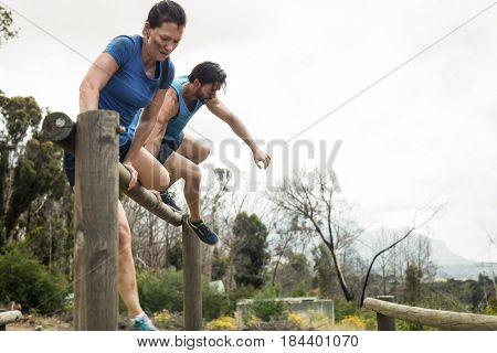 Couple jumping over the hurdles during obstacle course in boot camp