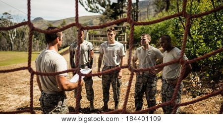 Male trainer instructing soldiers in the bootcamp