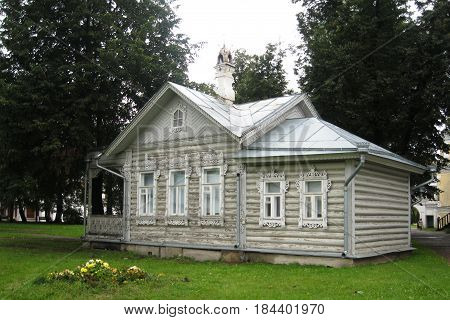 Traditional Russian wooden house with carved ornaments on the background of green trees and flowers. Five-walled cottage in the city of Vologda is traditional for northern regions. A small cottage is built of logs and painted with light paint whitewashed