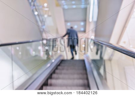 A man in a coat walks up the stairs of the escalator in the supermarket. Blurry