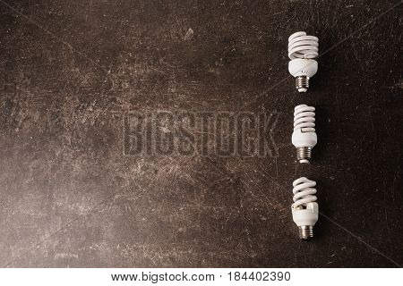 Fluorescent light bulb on a dark marble background with copyspace. To save energy concept with copyspace. Eco concept with copyspace