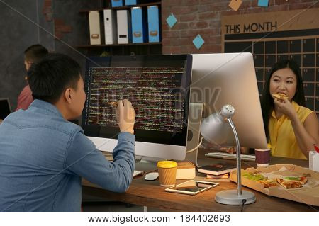Young programmers eating pizza while working in office